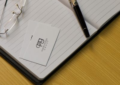 Logo for Olson Piceno Group on business card with journal